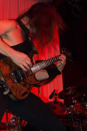Male guitarist performing at a live rock concert playing an electric guitar as he performs on stage under red spotlights with his hair obscuring his face photo