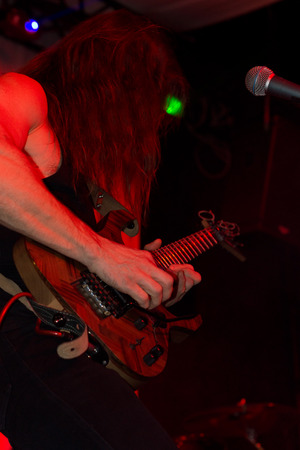 Male guitarist in a rock band playing an electric guitar performing live on stage in a nightclub or at a concert or festival under red lighting photo