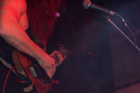 Closeup of the instrument and hands of a man playing electric guitar live on stage at a jazz or rock concert in atmospheric red lighting photo