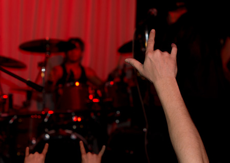 Rockers fans in the audience at a rock concert giving the horns sign or heavy metal gesture as they cheer for the musicians to come on stage at a live performance photo