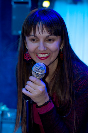 vocalist: Smiling attractive woman vocalist with long brunette hair standing holding the microphone singing in a rock or jazz convert in colourful, atmospheric blue lighting Stock Photo