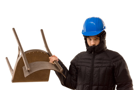 threateningly: Aggressive teenage hooligan in a balaclava and hardhat wielding a wooden chair standing glaring threateningly at the camera with it raised above his head, isolated on white