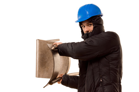 brandishing: Violent teenage hooligan in a hoodie and hardhat brandishing a wooden chair raising it above his shoulder as he prepares to attack, isolated on white