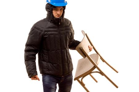aggressively: Angry giovane teppista adolescente in un cappuccio ed elmetto protettivo portando una sedia di legno sollevando in modo aggressivo mentre si prepara per una lotta, isolato su bianco