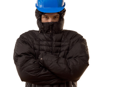 malevolent: Pugnacious young thug in a black balaclava and hardhat standing blocking the way with an angry expression and with folded arms, isolated on white Stock Photo