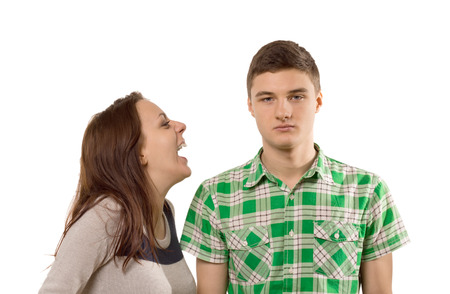 withdrawn: Young woman laughing at her own joke as he boyfriend stands looking unimpressed and unamused with a stony face, isolated on white