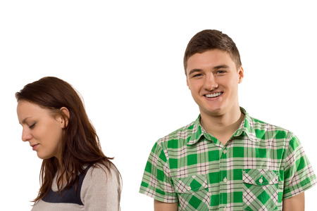 Inconsiderate unfeeling handsome young man smiling with pleasure as his girlfriend turns aside in tears upset at his oblivious attitude, isolated on white