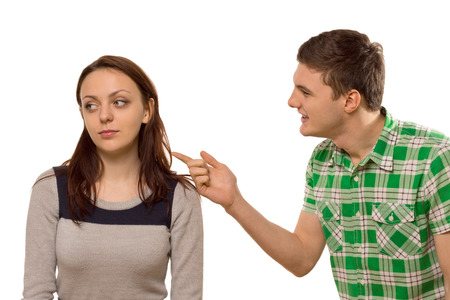 withdrawn: Young man arguing with his girlfriend pointing his finger at her as she turns aside in indifference, isolated on white