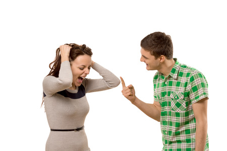 Young couple having a disagreement as the woman screams in anger and frustration at her boyfriend who is making a rude gesture with his finger, isolated on white Stock Photo