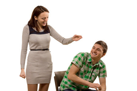 Laughing playful attractive young couple with the woman raising her hand in greeting as the man turns in his chair with a smile of happiness, isolated on white Stock Photo