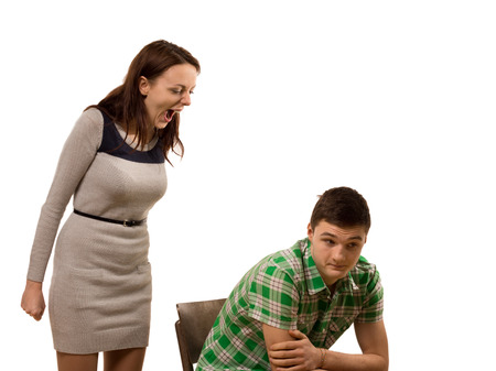 unresponsive: Attractive young woman standing shouting at her boyfriend as he sits in a chair with a resigned expression,isolated on white