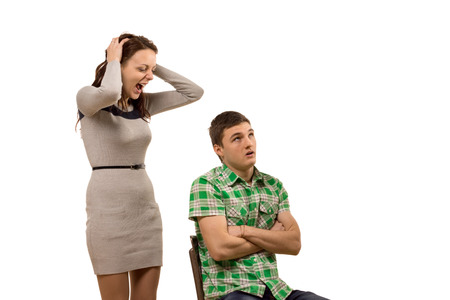 Young woman arguing with her boyfriend yelling at him as he sits in a chair with his arms folded staring upwards as he tries to control himself from retaliating, isolated on white