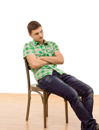 slumped: Handsome young man sitting slumped in a wooden chair with his arms folded staring down at the the ground with a thoughtful expression, isolated on white Stock Photo
