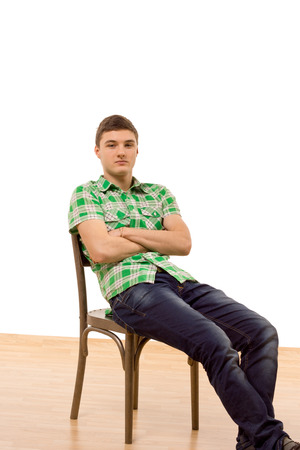 Confident young man sitting comfortably in an old wooden chair reclining backwards with his legs extended and arms folded as he looks thoughtfully ahead, isolated on white photo
