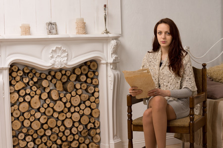 Elegant glamorous young woman in her living room sitting alongside an ornate marble fireplace with a document in her hands looking at the camera photo