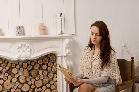 Elegant young woman in stylish clothes sitting reading in an armchair alongside an ornate marble fireplace stacked with logs photo