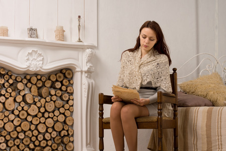 Elegant young woman in her living room sitting in a vintage wooden armchair alongside an ornate marble fireplace reading a document photo