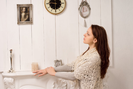 yearning: Nostalgic young woman in a stylish shawl standing with her hands resting on a marble mantelpiece looking at an old family portrait