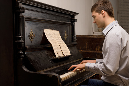 ivories: Young man practising at a piano for a recital reading sheet music from a tattered score, side view