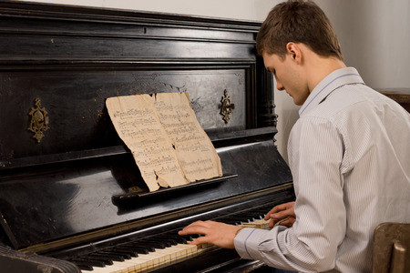 Young man enjoying playing an old nostalgic melody as he sits at an upright piano reading an old music score photo