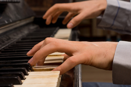 Close up of the hands of a male pianist playing music on an ivory keyboard on an old piano as he practices for a performance