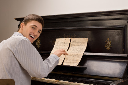 Young man laughing as he sits playing the piano turning to look at the camera in merriment as he enjoys himself photo