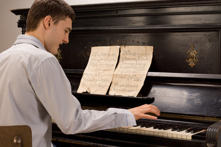 ivories: Young man having fun playing the piano smiling as he plays a melody from an old music score on a wooden upright piano