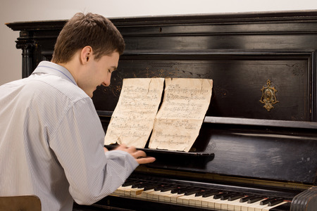 ivories: View from the rear of a young man smiling as he plays the piano using an old vintage music score on an upright wooden piano