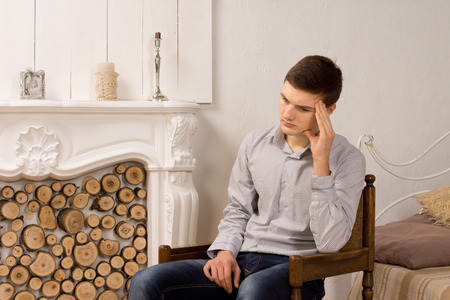 downhearted: Handsome stylish depressed young man sitting thinking in an old wooden chair in front of a marble fireplace with his head on his hand Stock Photo