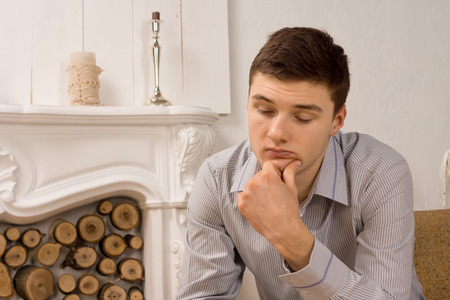 Sad depressed young man in a stylish shirt sitting in front of an ornate marble fireplace with downcast eyes and his chin on his hand
