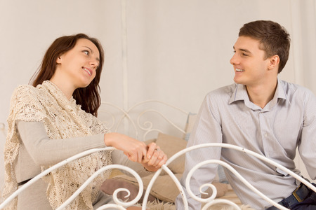 Smiling happy couple on a date with a stylish attractive young woman holding a wrought iron rail as she flirts with a handsome young man photo