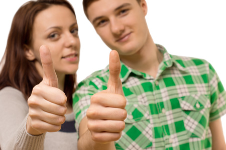Attractive happy smiling young couple giving a thumbs up of approval and success with selective focus to their thumbs photo
