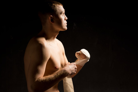 pugilist: Young boxer motivating himself mentally before a fight as he sits in the darkness applying a bandage to his fist