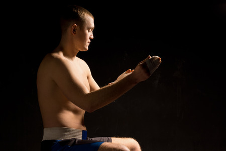 pugilist: Young pugilist boxer psyching himself up in the shadows as he bandages his fist before a fight Stock Photo