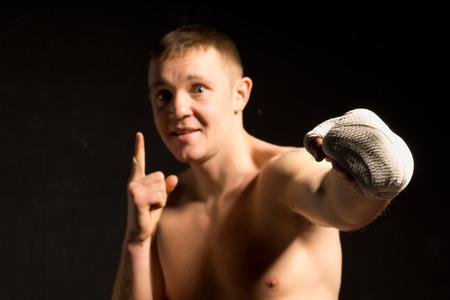 pugilist: Boxeador joven que lanza un pu�etazo durante una pelea de boxeo con pu�o vendado mientras hace un gesto con el dedo, oscuro imagen dram�tica en las sombras