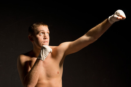 pugilist: Young male boxer standing in the darkness throwing an upwards punch as he limbers up before a fight with copyspace