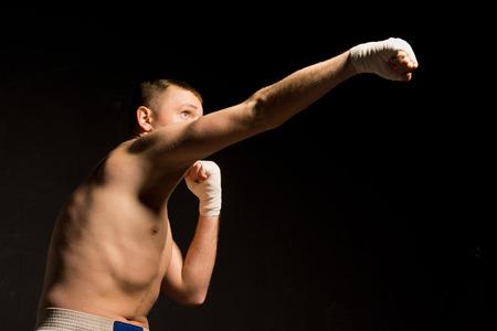 pugilist: �ngulo de visi�n baja en la oscuridad de un boxeador joven en forma lanzando un pu�etazo gancho de derecha con un brazo extendido Foto de archivo