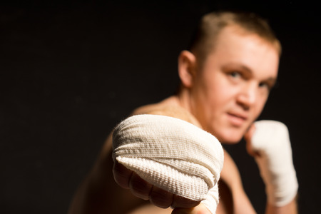 pugilist: Boxeador joven que lanza un sacador de gran alcance en la direcci�n de la c�mara con un pu�o vendado con enfoque a la mano
