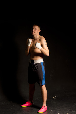 pugilist: Fit young boxer standing in the ready position in the darkness with his bandaged fists raised to his chest as he carefully watches his opponent