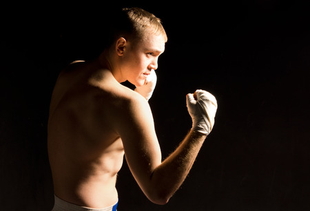 pugilist: Young boxer squaring off during training raising his fists while closely watching his opponent for a move or opening in a dark atmospheric portrait