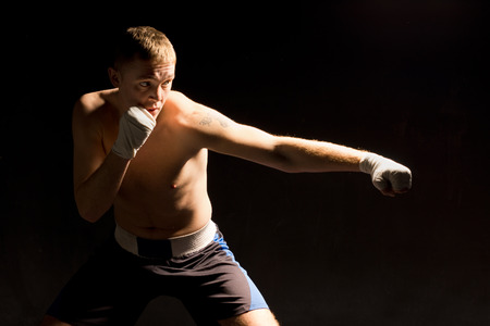 pugilist: Pugnacious young boxer throwing a punch during a fight with a look of determination against a dark shadowy background