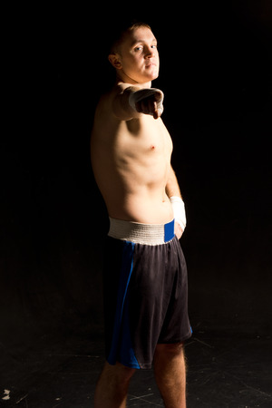 pugilist: Muscular young boxer in his shorts pointing his bandaged hand at the camera while standing barechested in the darkness Stock Photo