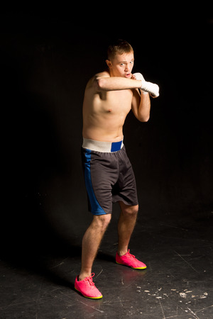 warming up: Young boxer training before a match working out in the ring throwing punches with his bandaged fists on a dark background