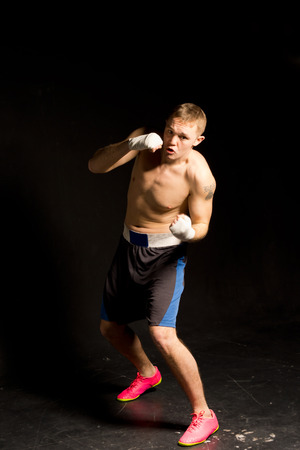 limbering: Determined boxer throwing a jab facing the camera as he punches the air during a work out in the ring