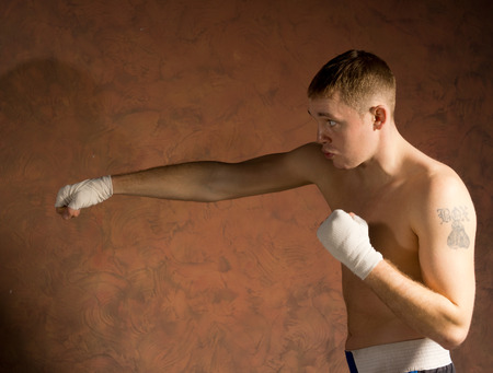 warming up: Young boxer in training throwing a punch with bandages on his fists as he works out in the ring, with copyspace