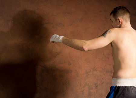 limbering: Boxer standing ready for his opponent waiting to deflect a blow against a dark brown background showing his opponents shadow, close up view from the side