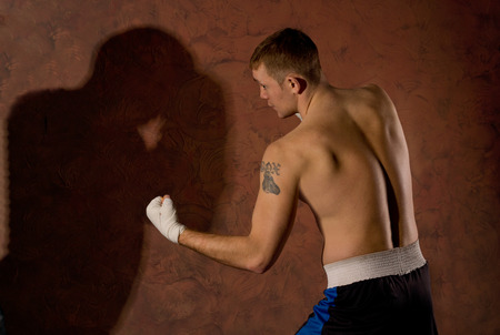 Fit young boxer fighting in the ring squaring off with his fists at the ready and the shadow of his opponent facing him on the wall photo