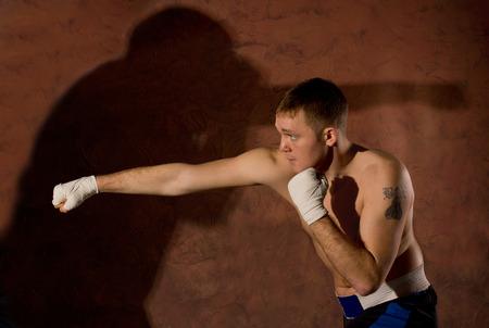 pugilist: Boxeador joven golpear a un adversario durante una pelea en el ring con el pu�o extendido y la sombra de su oponente lanz� en la pared detr�s de �l