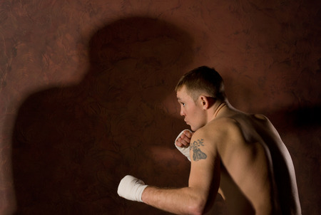warming up: Young determined boxer in a fight standing crouched forward with his bandaged fists raised, side view with copyspace