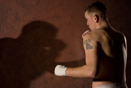limbering: Two boxers fighting with one young man standing with his back turned to the camera squaring off against an opponent whose shadow is seen on the brown wall Stock Photo